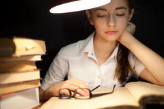 Young girl reading book under lamp Royalty Free Stock Image