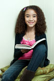 Young girl reading in corner stock image