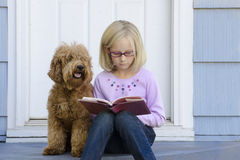 Young girl reading with dog. A serious young girl sits on the steps of her house reading a book with her dog next to her Royalty Free Stock Photo