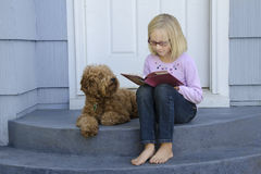 Young girl reading with dog at side Stock Image