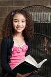 Young girl reading by fireplace Stock Image