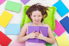 Young girl reading on the floor Royalty Free Stock Photos