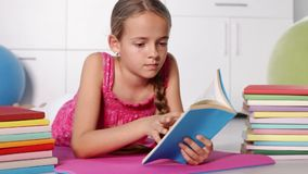 Young girl reading on the floor. Turning page, camera dolly stock video
