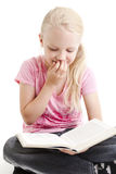 Young girl reading funny book stock photography