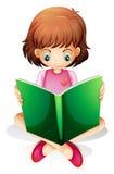 A young girl reading a green book Stock Photo