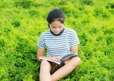 Young girl reading in green meadow contryside nature in evening. Light vintage style Stock Image
