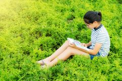 Young girl reading in green meadow contryside nature in evening. Light vintage style Royalty Free Stock Images