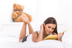 Young girl reading her book in bed. Royalty Free Stock Photos