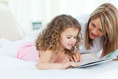 Young girl reading with her grandmother. Young girl reading a book with her grandmother Stock Photos