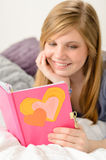 Young girl reading her journal of memories. Friendly young girl reading her journal of memories Royalty Free Stock Image