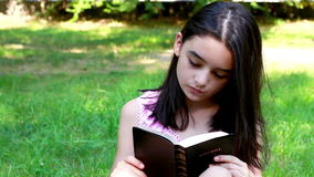 Young girl reading Holy Bible.