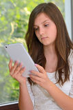 Young girl reading information on a tablet computer Royalty Free Stock Photo