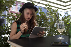 Young girl reading on iPad in a caffe enjoying summer. Young girl writing in a caffe with glass of lemonade and iPad stock photo