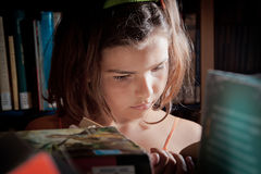 Young girl reading in a library Stock Photography