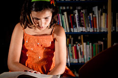 Young girl reading in a library Stock Images