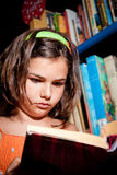 Young girl reading in library Stock Image
