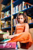 Young girl reading in a library Royalty Free Stock Photo