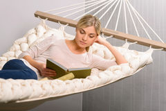 Young girl is reading while lying in the hammock Stock Image