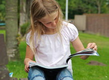 Young girl reading magazine Royalty Free Stock Images