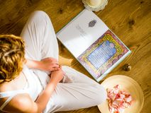 Young girl reading the bhagavad gita in the light of the setting suns royalty free stock photography