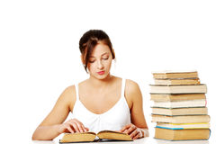 Young girl reading near pile of books. Royalty Free Stock Photos