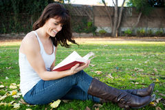 Young girl reading in park Stock Photos