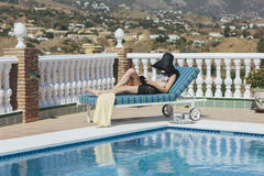 Young girl reading by the pool Royalty Free Stock Photos