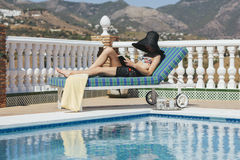 Young girl reading by the pool Stock Photos