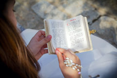 Young girl reading prayer book. Young girl reading a prayer book with spanish text in her First Holy Communion Royalty Free Stock Photos