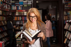 Young girl reading something funny. Close-up of attractive young girl with geeky eyeglasses in bookshop reading something from a book and laughing, ith other royalty free stock photo