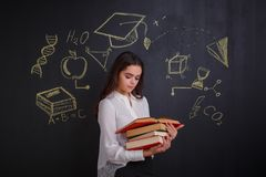 Young girl reading a stack of different books, standing next to a whiteboard. royalty free stock photo
