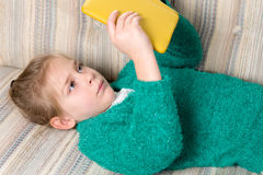 Young Girl Reading Tablet on the Sofa Royalty Free Stock Images