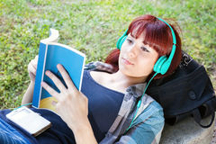 Young girl reads a book and listening to music Royalty Free Stock Photo