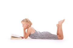 Young girl reads a book lying down Royalty Free Stock Image