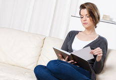 Young girl reads the book sitting on the sofa Royalty Free Stock Image