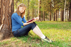 The young girl reads the book under a tree Royalty Free Stock Image