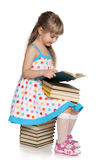 Young girl reads on the pile of books Stock Photos