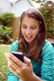 Young girl reads a surprising message. Young teenager reading a text message on a cellphone Royalty Free Stock Images