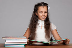 Young girl reads at the table Royalty Free Stock Photography