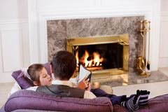 Young girl reads to her Dad. Father and daughter sit and read by the fire stock image