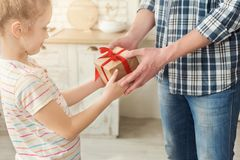 Young girl receiving a gift from her father. Young girl receiving gift from her father. Dad surprising his little daughter with present, copy space Royalty Free Stock Photo