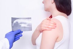 A young girl at the reception at the doctor is holding her shoulder on a white background, the doctor is holding a needle with stock photography