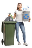 Young girl with a recycling bin and a garbage bag. Full length portrait of a young girl with a recycling bin and a garbage bag next to a trash can isolated on Stock Image