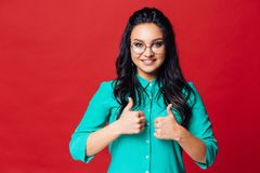A young girl on a red background shows with her fingers that she is in a good mood. Pretty fashion cool elegance woman with hair bun in glasses as indicated at royalty free stock images