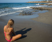 Young girl in red bikini and her shadow. On the beach of Crete in Greece stock image