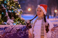 Young girl in a red cap standing at the Christmas tree on Christ Royalty Free Stock Image