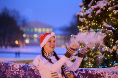 Young girl in a red cap stands near a Christmas tree. She throws royalty free stock photography