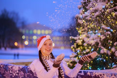 Young girl in a red cap stands near a Christmas tree. She throws Stock Image