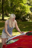 A young girl with a red car Stock Images