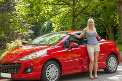 A young girl with a red car Royalty Free Stock Photos